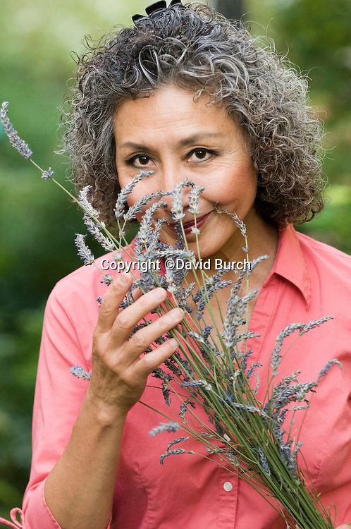 Asian woman smelling lavendar in her garden