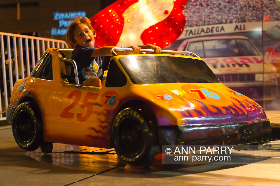 August 7, 2012 - Merrick, New York, U.S. - On Speedway children's ride, a young boy rides race car around track, the first night of the 22nd Annual Merrick Festival on Long Island.