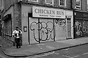 London, UK. 04.04.2015. Man on his phone outside Chicken Run shop, East London. Photograph © Jane Hobson.