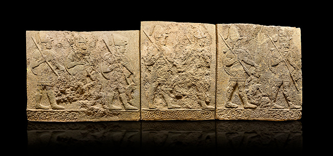 Hittite sculpted orthostats panels of Long Wall Limestone, Karkamıs, (Kargamıs), Carchemish (Karkemish), 900-700 B.C. Soldiers. Anatolian Civilisations Museum, Ankara, Turkey<br /> <br /> Figures of helmeted warriors. They have their shield in their back and their spear in their hand. The prisoner in their front is depicted as small. The lower part of the orthostat is decorated with braiding motifs. <br /> <br /> On a black background.