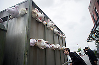 """Banksy enthusiasts flock to the trendy Meatpacking District in New York on Friday, October 11, 2013 to see the eleventh installment of Banksy's art, """"The Sirens of the Lambs"""". This particular sculptural piece consists of a slaughterhouse truck filled with bleating plush animals, controlled by puppeteers, which were driven around by a driver, who remained in character. The elusive street artist is creating works around the city each day, during the month of October accompanied by a satirical recorded message parodying a museum tour which you can get by calling the number 1-800-656-4271 followed by  # and the number of artwork.  (© Frances M. Roberts)"""