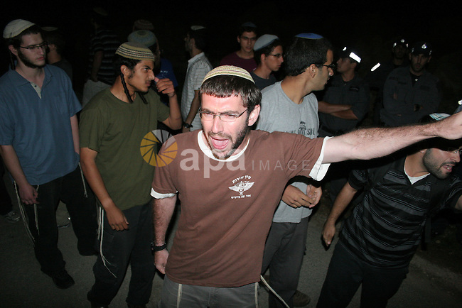 Israeli settlers express their anger in front of Israeli policemen after a settlers car was ambushed by Palestinian gunmen killing two woman and two men next to Kiryat Arba settlement in the southern West Bank August 31, 2010. The military wing of the Islamist Hamas said it was behind the killing of four Israelis in an attack near the West Bank settlement of Kiryat Arba today. Photo by Mamoun Wazwaz