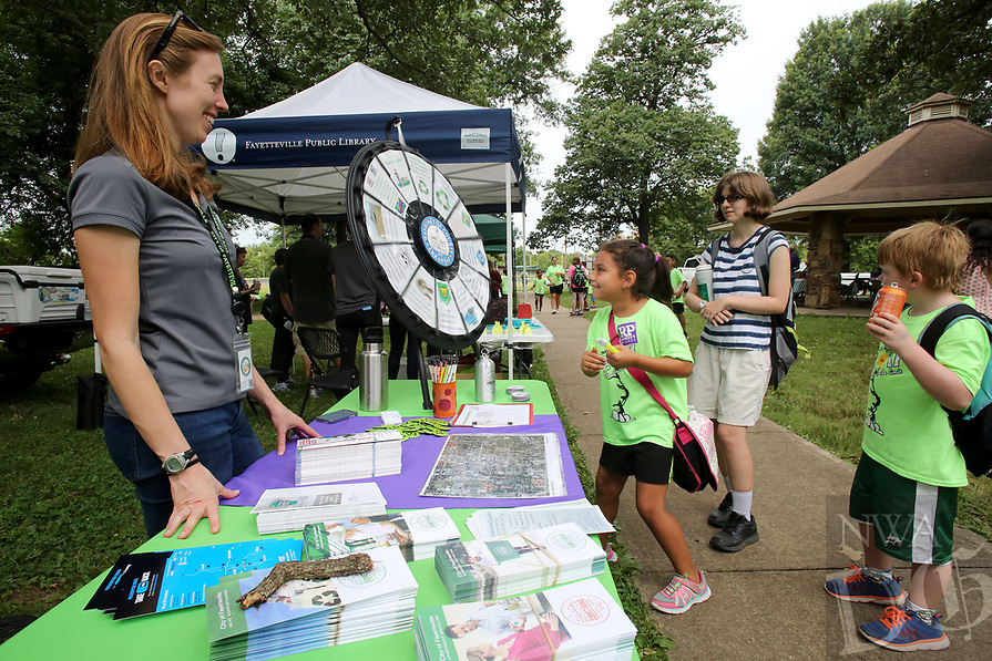 NWA Democrat-Gazette/DAVID GOTTSCHALK  Rachel Kraus (from left), with the city of Fayetteville Recycling and Trash Collection Division, watches Friday July14, 2017 Maggie Mancia, Leah Tripp and Elliot Chyrchel spin an quiz wheel  at the 10th annual CDBG in the Park picnic at the Walker Park Pavilion in Fayetteville. The city's Community Development Block Grant held the picnic to share  information with  citizens about the programs that CDBG has to offer and to celebrate its investment in the community.  The event featured a free lunch, cold treats, family-friendly activities and information booths.
