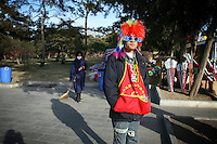 CHINA. A man during Chinese New Year in Ditan Park in Beijing.  Chinese New Year, or Spring Festival, is the most important festival and holiday in the Chinese calendar In mainland China, many people use this holiday to visit family and friends and also visit local temples to offer prayers to their ancestors. The roots of Chinese New Year lie in combined influences from Buddhism, Taoism, Confucianism, and folk religions.  2008.