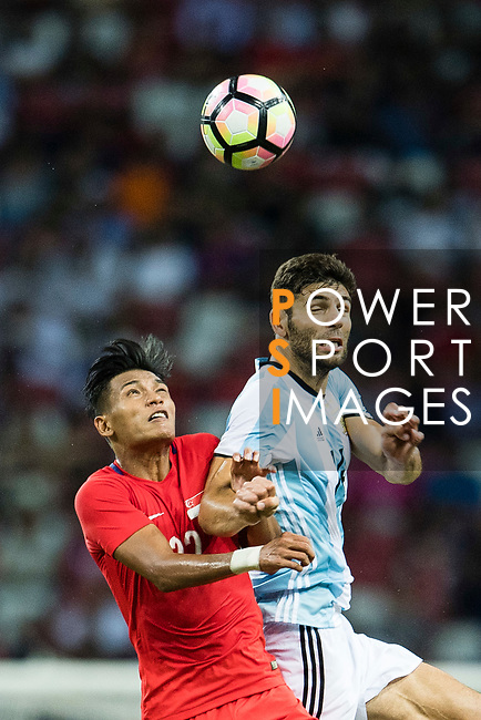 Khairul Nizam of Singapore (L) fights for the ball with Federico Fazio of Argentina (R) who heads the ball during the International Test match between Argentina and Singapore at National Stadium on June 13, 2017 in Singapore. Photo by Marcio Rodrigo Machado / Power Sport Images
