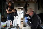 Snow Leopard (Panthera uncia) veterinarian, John Ochsenreiter, preparing snow leopard blood samples while volunteer, David Cooper, looks on, Sarychat-Ertash Strict Nature Reserve, Tien Shan Mountains, eastern Kyrgyzstan