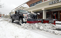 A plow truck clears the way in the Barracks Road Shopping Center Thursday after a snowfall in Charlottesville, VA. Photo/Andrew Shurtleff