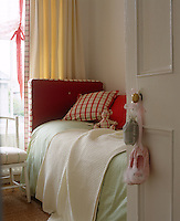 In this cheerful child's bedroom a pretty red-and-white ginghan cushion comes with a matching teddy bear