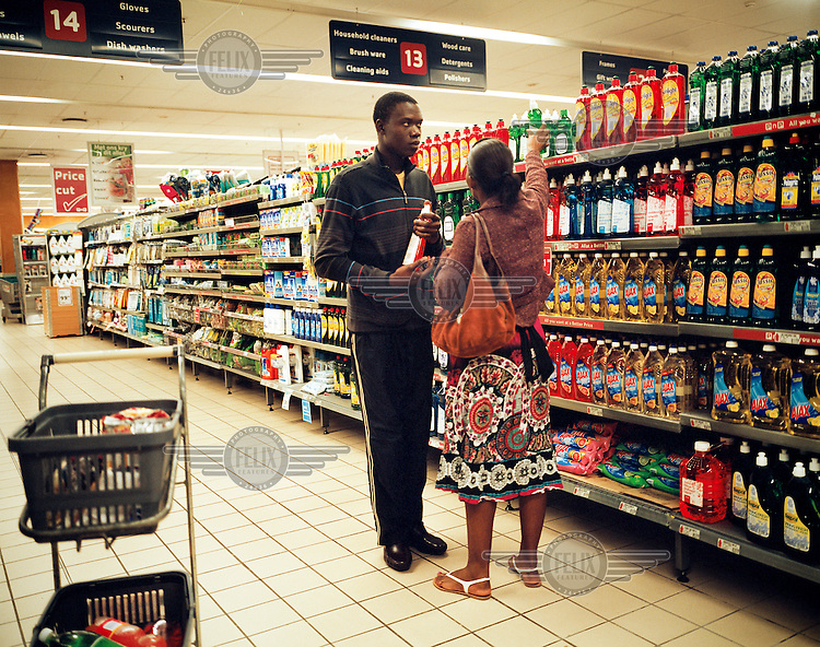 A Mozambican couple shopping in a supermarket in South Africa, where goods are cheaper and more plentiful than in their in own country. /Felix Features
