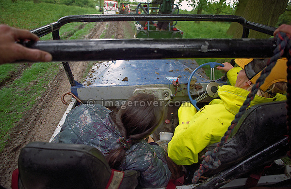 At the 1993 A.R.C. National Rally travelling to the next section on the back of a Land Rover Series 1 based off-road racer. The Association of Rover Clubs (A.R.C., since 2006 the Association of Land Rover Clubs ALRC) National Rally is the biggest annual motor sport oriented Land Rover event and was hosted 1993 by the Midland Rover Owners Club at Eastnor Castle in Herefordshire. --- No releases available. Automotive trademarks are the property of the trademark holder, authorization may be needed for some uses.