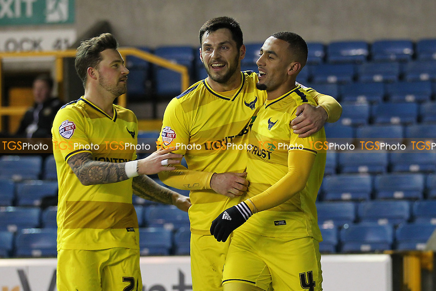 Kemar Roofe of Oxford United (R) scores the first goal for his team and celebrates with his team mates during Millwall vs Oxford United at The Den