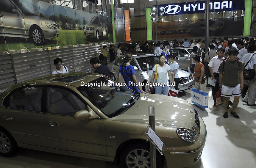 Chinese visitors look at Hyuandai cars at the Auto China 2004 exhibition in Beijing, China..