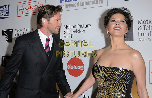 "HUGH JACKMAN  & CATHERINE ZETA JONES .at The 4th Annual ""A Fine Romance"" held at Sony Picture Studios in Culver City, California, USA,  November 08 2008.                                                                     .half length strapless black gold print dress hair up long maxi  jewel encrusted beaded grey gray suit pink striped tie holding hands .CAP/DVS.©Debbie VanStory/Capital Pictures"