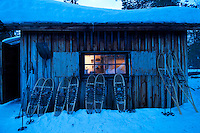 "Solberget, Jokkmokk, Swedish Lapland, Sweden, March 2013. After a couple of hours snowshoeing we reach a little hut on one of the hills. Dirk and Silke Hagenbusch live their lives in a wilderness retreat  called 'Solberget'. It is situated directly on the Arctic Circle, near the nature reserves ""Granlandet"", ""Päivavuoma"" and ""Pellokiellas"", and close to the ""Muddus"" National Park. Here, nature can be experienced in its purest form – far away from civilisation. As an authentic wilderness farm, Solberget is neither connected to public electricity nor to the mains water supply. Water comes from a spring in the woods and is delicious! Oil lamps and the natural warmth of wood burning stoves provides a soft and cosy atmosphere, even with biting frost outside. Photo by Frits Meyst/Adventure4ever.com"