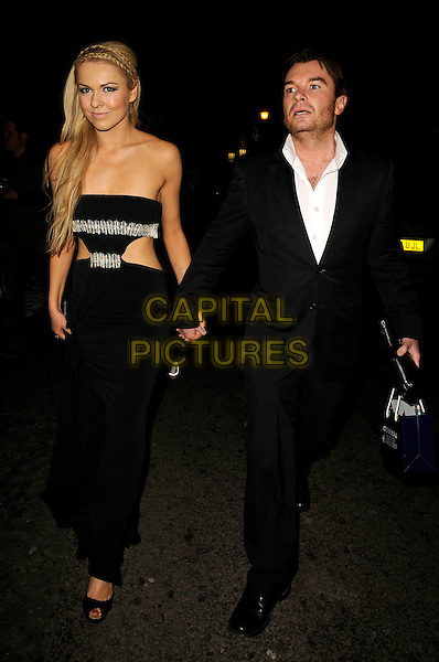 ZOE SALMON & GUEST.Digital Spy Reality TV Awards at the Bloomsbury Ballroom, London, England.  .April 6th, 2009.full length black strapless dress silver straps cut out away long maxi holding hands black suit.CAP/CAN.©Can Nguyen/Capital Pictures.