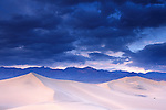 Storm clouds in evening over sand dunes and mountains, Stovepipe Wells, Death Valley National Park, California
