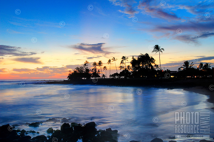 Sunset from Brennecke's Beach Poipu, Kaua'i, with palm trees and the evening lights in the distance.