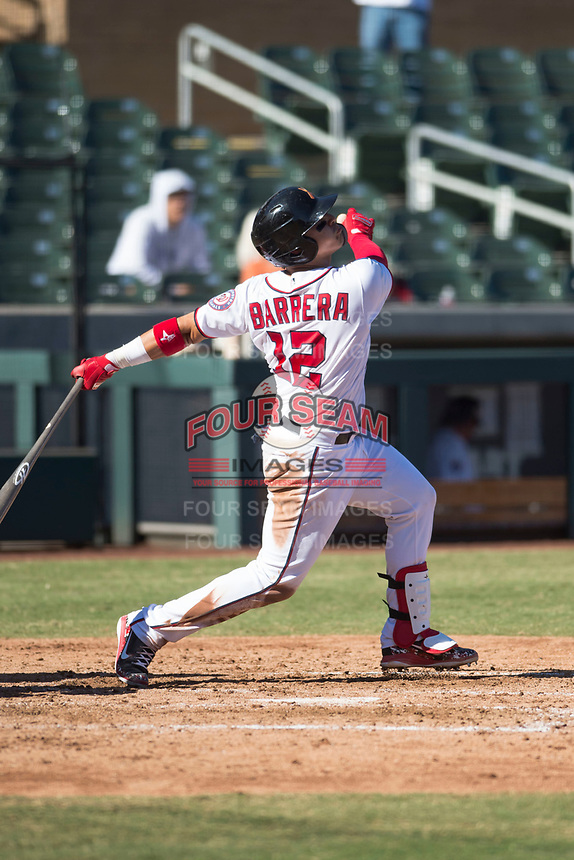 Salt River Rafters catcher Tres Barrera (12), of the Washington Nationals organization, follows through on his swing during an Arizona Fall League game against the Glendale Desert Dogs at Salt River Fields at Talking Stick on October 31, 2018 in Scottsdale, Arizona. Glendale defeated Salt River 12-6 in extra innings. (Zachary Lucy/Four Seam Images)