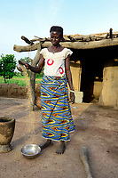 BURKINA FASO, Dano, Fondation Dreyer, rice farming, woman with rice bowl , winnowing to separate grain from chaff/ Reisanbau in Talauen, Frau des Reisbauern Somda Galip auf ihrem Hof, Schale mit Reis, die Spreu vom Korn trennen
