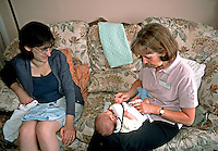 Midwife on a home visit. She is visiting mother and newborn baby at home where she will check the infant and will give the mother advice and deals with any worries or concerns. This image may only be used to portray the subject in a positive manner..©shoutpictures.com..john@shoutpictures.com
