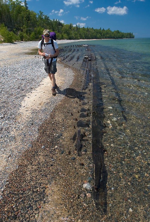A backpacker hikes past a shipwreck on a beach near Au Sable Point in Pictured Rocks National Lakeshore near Grand Marais, Mich.