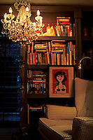 A lit crystal chandelier hangs above an armchair in the corner of a room. Behind are books and pottery peices displayed on a shelving unit giving the room a cosy and compact feel.