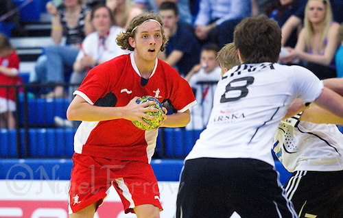 11 JUN 2010 - LONDON, GBR - Alexander Girvan (Great Britain - red) looks for a way through the Estonian defence (white and black) during the two teams 2012 European Handball Championships Qualification Tournament match (PHOTO (C) NIGEL FARROW)