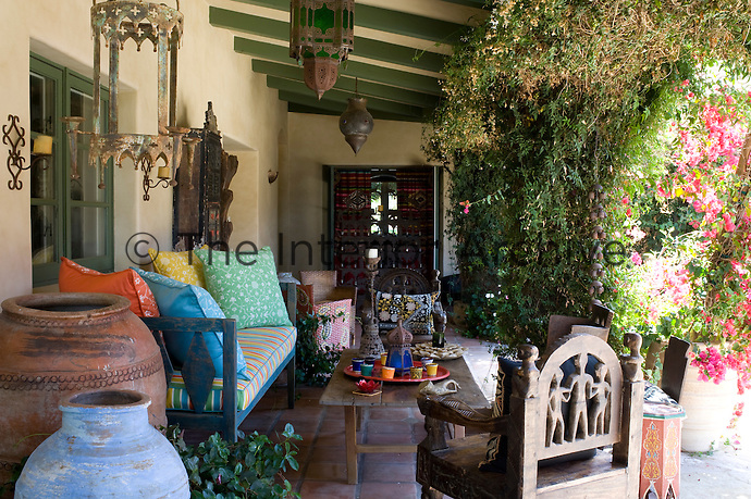 The covered terrace is furnished with wooden African furniture and decorated with Moroccan lanterns