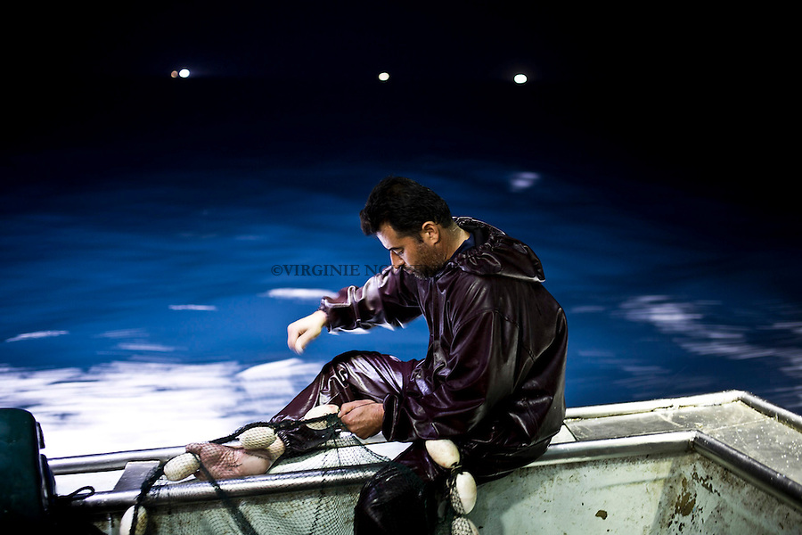 Gaza sea: Majed is sewing the holes of the net.<br /> <br /> Mer de Gaza: Majed recoud les trous du filet.