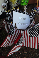 Phoenix, Arizona. July 3, 2013. A small makeshift memorial for the 19 Arizona firefighters who died on June 30 battling the Yarnell Hill wildfire was built outside the Forensic Science Center in Phoenix, where autopsies are being conducted. Garret Zuppiger, 27, is honored in the memorial built to pay tribute to the victims of one of the most horrible tragedies involving firefighters in the United States. Photo by Eduardo Barraza © 2013