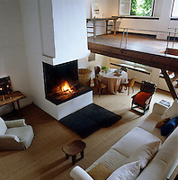 A view from the mezzanine down to the open-plan living area which is dominated by a large fireplace