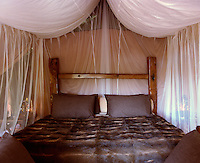A rustic bed with a fur cover is draped in mosquito netting in one of the bedroom tents