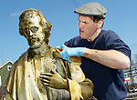 WATERBURY CT. 16 March 2018-031919SV05-Rev. Jim Sullivan pours water over St. Joseph while cleaning the statue with Sacred Heart High students at the St. Joseph Cemetery in Waterbury Tuesday. Tuesday March 19th was St. Joseph Day. <br /> Steven Valenti Republican-American