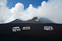 The main crater behind Mercedes Unimogs bringing tourists up the vast slopes of Mount Etna, Sicily's 3.350 m high active Vulcano.