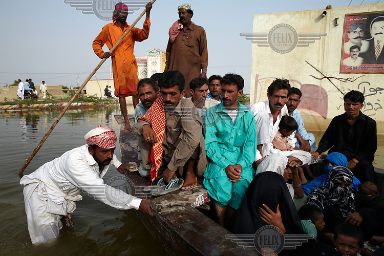 People use boats to travel from the town of Johi, which has been cut by flood water, in Sindh province, Pakistan.
