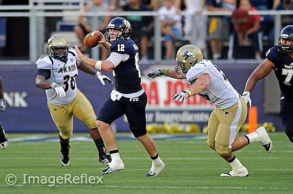 8 September 2012:  FIU quarterback Jake Medlock (12) passes while scrambling in the second quarter as the FIU Golden Panthers defeated the Akron Zips, 41-38 (overtime), at FIU Stadium in Miami, Florida.