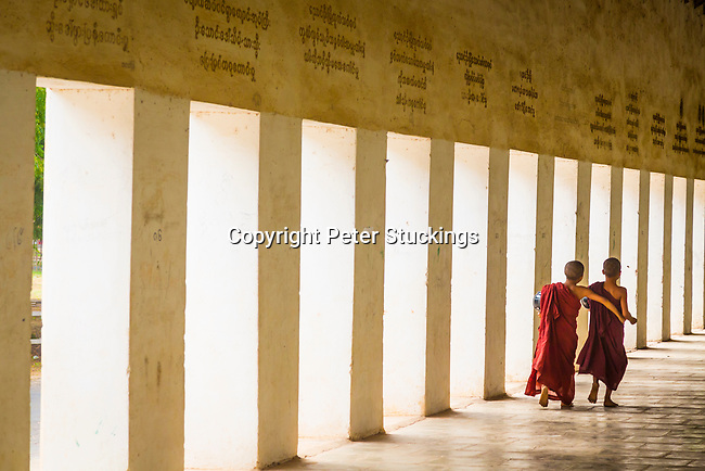 Novice monks walk through the corridor at Shwesigon Pagoda, Myanmar