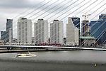 ROTTERDAM - In Rotterdam vaart een waterbus op de rivier de Maas onder de door Ben van Berkel ontworpen Erasmusbrug waar een roze met reclame volgeplakte tram van de RET oprijdt. De tuibrug die het centrum van de stad verbindt met de kop van Zuid, maakte tevens de onsluiting van de Wilhelminakade en de Rotterdamse stadsdeel Oud Zuid mogelijk. Op de achtergrond zijn diverse woontorens en kantoortorens van Robeco en Ernst & Young zichtbaar, evenals de bouw van een nieuwe mini wolkenkrabber. COPYRIGHT TON BORSBOOM