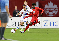 TORONTO, ON - OCTOBER 15: Daniel Lovitz #5 of the United States and Alphonso Davies #12 of Canada get after a loose ball during a game between Canada and USMNT at BMO Field on October 15, 2019 in Toronto, Canada.