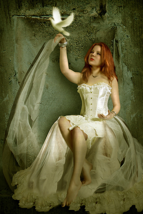Young girl with red hair sitting wearing a silk corset with white dove