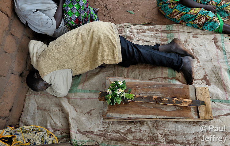 A Congolese father grieves beside the casket containing the body of his 8-month old daughter who died of malaria in Mwitobwe, in the Democratic Republic of the Congo.