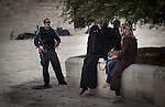 Two palestinian women talk beside Al Aqsa mosque in the Esplanade of the Mosques, while they have the close surveillance of a israeli soldier, in East Jerusalem.