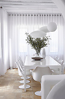 Retro style pendant lights hanging above a simple white dining table and Eero Saarinen chairs. The room has a stone tiled floor and full length white curtains.