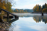 Idaho, Silver Valley, Rose Lake. Reflections in the water with rising mist and autumn colors. An old log launch for sliding logs into the river for transport on the left.