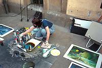Sidewalk artist age 19 working on a painting.  Krakow Poland