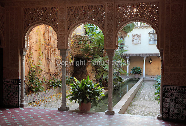 Patio Nazari, developed in 1944 in Moorish style, taking inspiration from parts of the Alhambra, in the Carmen de los Martires Garden, on the site of a Barefoot Carmelite shrine and convent originally established in 1492, in Granada, Andalusia, Southern Spain. In the centre is a long pond, here seen through a pavilion with horsehoe arch colonnade. A Carmen is a traditional house with enclosed garden, this example dates to the 19th century and displays various garden styles including English, Spanish and Nasrid. Picture by Manuel Cohen