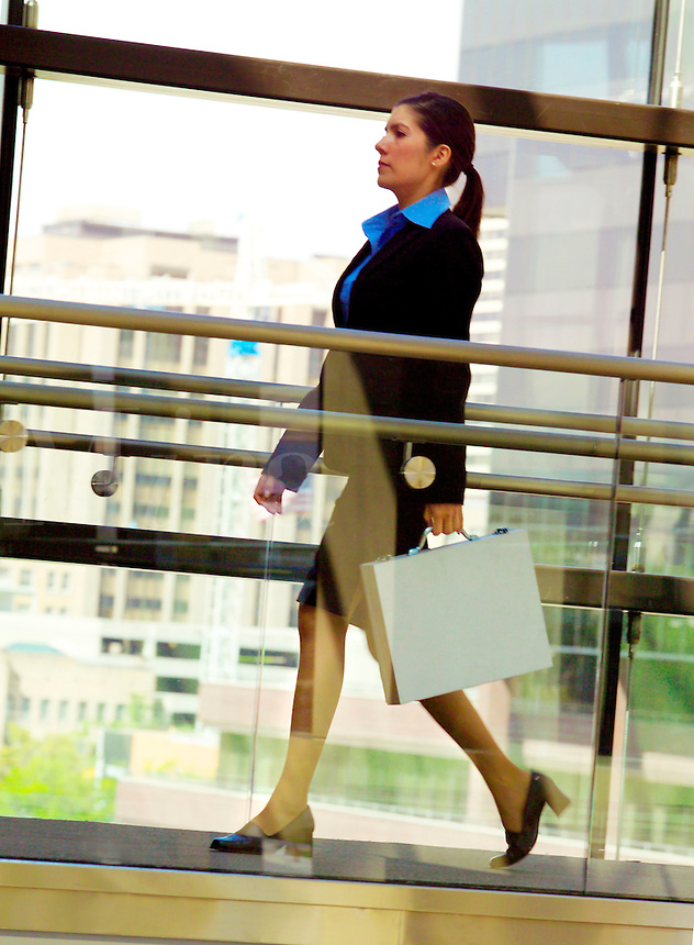 Successful business woman in business suit walking with briefcase