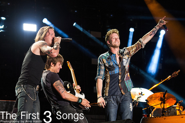 Keith Urban performs with Brian Kelly and Tyler Hubbard of Florida Georgia Line at LP Field during Day Three of the 2014 CMA Music Festival in Nashville, Tennessee.