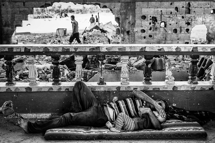 Gaza, Beit Hanoun: Abdel Abu Ouda et son fils se reposent dans le salon de leur maison &agrave; moiti&eacute; d&eacute;truite lors des bombardements de l&rsquo;&eacute;t&eacute; 2014. 21/10/2014<br /> <br /> Gaza, Beit Hanoun: Abdel Abu Ouda,  and his son are resting in the living room of their house half destroyed during the bombing of summer 2014. 21/10/2014