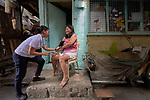 Zeni Delfin, a student in the Mary Johnston College of Nursing in Manila, takes the blood pressure of Maria Theresa Guillen in front of Guillen's home in the Parola neighborhood of Manila's Tondo section. Delfin and other nursing students regularly visit the neighborhood to do health education and monitor the health of residents. The students also run a feeding program for neighborhood children.<br /> <br /> The nursing school is supported by United Methodist Women.